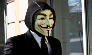 An individual wearing a suit and Guy Fawkes Anonymous mask at a Scienology protest in Minneapolis, Minnesota.
